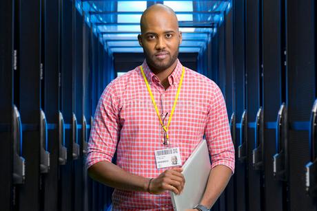 Portrait Of IT Technician In Data Centre Standing By Serversの写真素材 [FYI02122815]