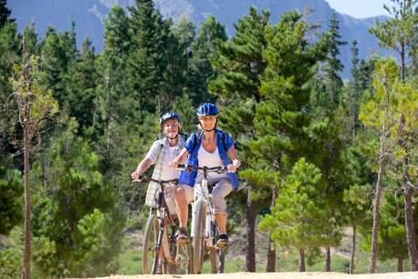 Older couple riding mountain bikes in forestの写真素材 [FYI02122821]