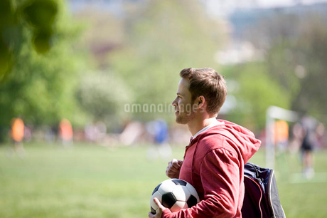 A young man standing in the park, carrying a football and a sports bagの写真素材 [FYI02122822]
