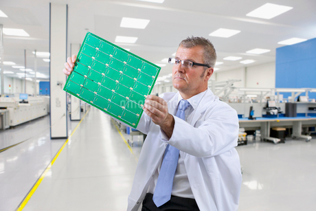 Technician Examining Printed Circuit Board In Electronics Factoryの写真素材 [FYI02122851]