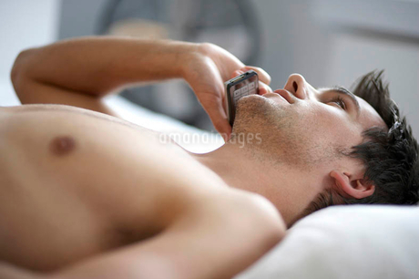 Young man laying on a bed talking on a mobile phone, close-upの写真素材 [FYI02122853]
