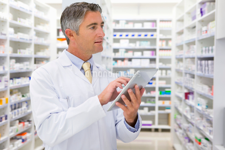 Male Chemist With Digital Tablet Working In Pharmacyの写真素材 [FYI02122856]