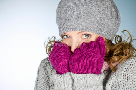 A young woman wearing hat and gloves, trying to keep warmの写真素材 [FYI02122869]