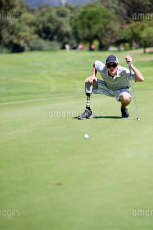 Male Golfer With Artificial Leg On Course Lining Up Ball On Greenの写真素材 [FYI02122873]
