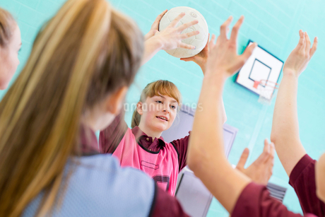 High school students playing volleyball in gym classの写真素材 [FYI02122880]