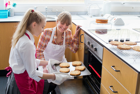 Teacher teaching high school student removing baked cookies from oven in home economics classの写真素材 [FYI02122893]