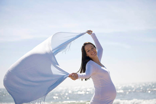 A pregnant woman on the beach, holding a scarf into the windの写真素材 [FYI02122896]