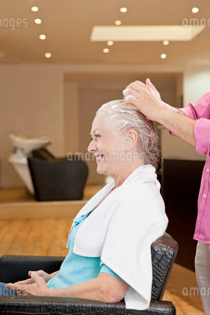 A male hairdresser applying product to his female clients hair, close upの写真素材 [FYI02122925]