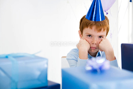 boy sulking at birthday partyの写真素材 [FYI02122935]