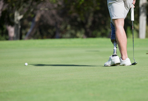 Close Up Of Male Golfer With Artificial Leg Putting Ball On Greenの写真素材 [FYI02122938]