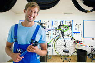 Cycle technician smiling at camera in workshopの写真素材 [FYI02122954]