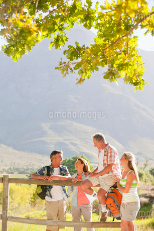 Two generation family out for walk resting on fence in countrysideの写真素材 [FYI02122986]