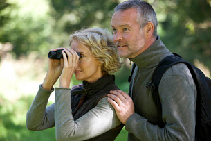 A mature couple outdoors, woman looking through a pair of binocularsの写真素材 [FYI02123023]