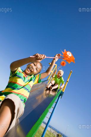 Boys holding pinwheels on slide at playgroundの写真素材 [FYI02123058]
