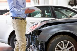 Insurance assessor inspecting damaged vehicleの写真素材 [FYI02123077]