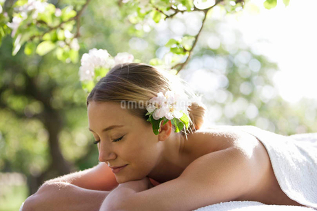 A young woman laying on a massage table under a tree in blossom, eyes closedの写真素材 [FYI02123096]