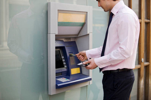 A businessman using a cash machineの写真素材 [FYI02123105]