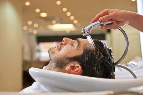 A male hairdresser rinsing a male clients hairの写真素材 [FYI02123108]