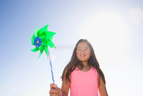 Smiling girl playing with pinwheel outdoorsの写真素材 [FYI02123110]