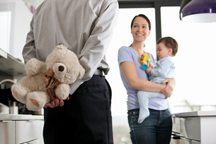 A man returning home to his family after work, holding a teddy bear behind his backの写真素材 [FYI02123117]