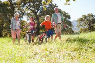 Grandparents and grandchildren pushing mountain bikes in rural fieldの写真素材 [FYI02123120]