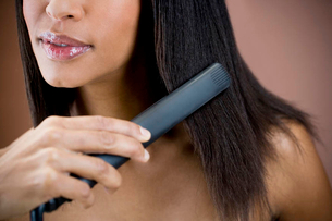 A woman straightening her hairの写真素材 [FYI02123133]