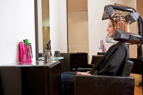 A female client looking at herself in a mirror in a hairdressing salonの写真素材 [FYI02123134]