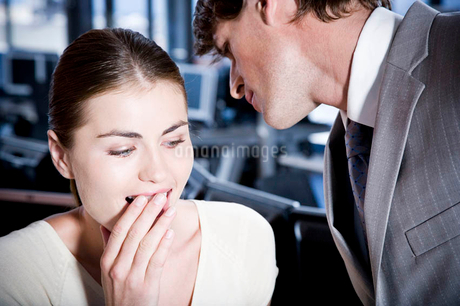 Two business colleagues whispering to each otherの写真素材 [FYI02123165]