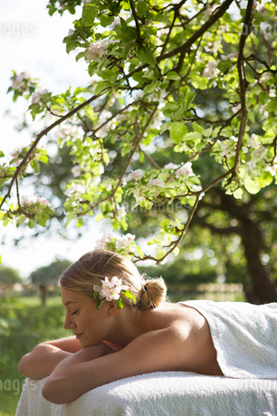A young woman laying on a massage table under a tree in blossom, eyes closedの写真素材 [FYI02123171]