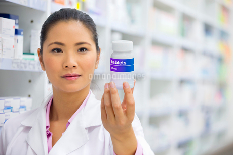 Pharmacist holding up medication potの写真素材 [FYI02123175]