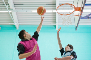 High school students playing basketball in gymの写真素材 [FYI02123195]