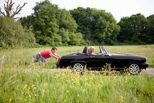 A young man pushing a black sports car, a woman in the driving seatの写真素材 [FYI02123210]
