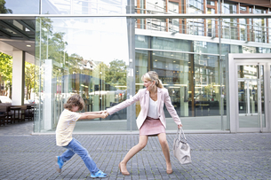 Businesswoman Pulling Reluctant Son Along Outside Officeの写真素材 [FYI02123227]