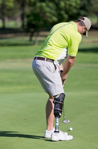 Male Golfer With Artificial Leg On Course Putting Ball On Greenの写真素材 [FYI02123241]