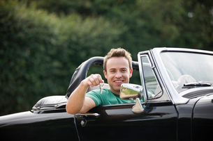 A young man sitting in a black sports car holding the keysの写真素材 [FYI02123249]