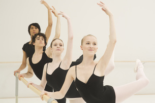 A group of young male and female ballet dancers practicing at the barreの写真素材 [FYI02123254]