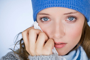 A young woman crying, wiping her tears away with a tissue, close-upの写真素材 [FYI02123255]