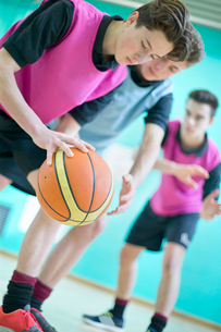 High school students playing basketball in gym glassの写真素材 [FYI02123272]