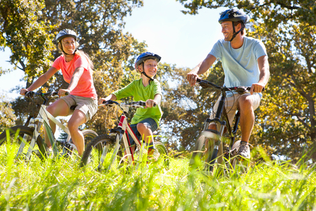 Family riding mountain bikes in rural fieldの写真素材 [FYI02123327]