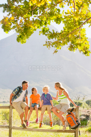 Two generation family out for walk resting on fence in countrysideの写真素材 [FYI02123329]