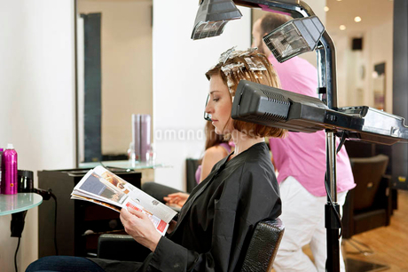 A female client reading a magazine whilst she has her hair coloured in a hairdressing salonの写真素材 [FYI02123339]
