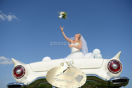 Bride Throwing Bouquet From Open Top Car On Wedding Dayの写真素材 [FYI02123352]
