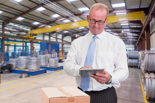 Businessman In Warehouse Dispatch Area With Digital Tabletの写真素材 [FYI02123354]
