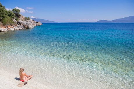 Woman, looking out to sea, sitting on sunny beachの写真素材 [FYI02123357]