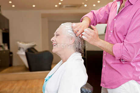 A male hairdresser applying product to his female clients hair, close upの写真素材 [FYI02123386]