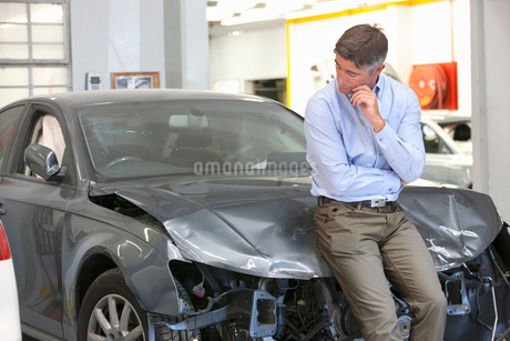 Car owner inspecting damaged vehicleの写真素材 [FYI02123391]