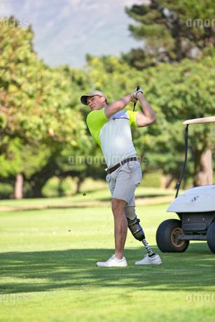 Golfer With Artificial Leg Hitting Ball On Fairwayの写真素材 [FYI02123402]
