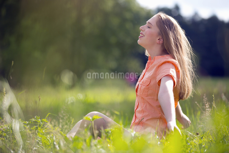 Attractive Woman Sitting In Countryside And Relaxingの写真素材 [FYI02123404]