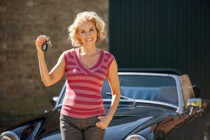 A mature woman holding the keys to classic sports carの写真素材 [FYI02123415]
