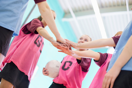 High school students touching hands in huddle before volleyball gameの写真素材 [FYI02123428]